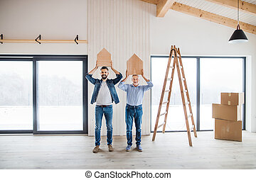 Two men holding small wooden houses on their heads when furnishing new house.