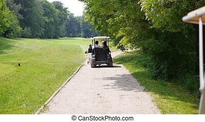 Two men in a golf car driving behind walking people