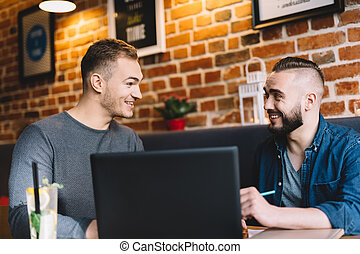 Two men in a good mood sitting by the laptop