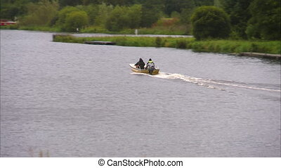 Two men in a small speedboat drive away - Two men in a small...