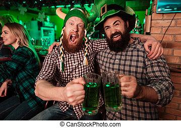 Two men in carnival caps celebrate St. Patrick's Day.