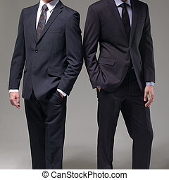Two men in elegant suit on a dark background
