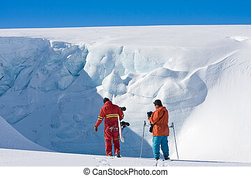 Two men in front of a wall of snow