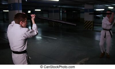 Two men in kimono training their kendo skills on a parking...