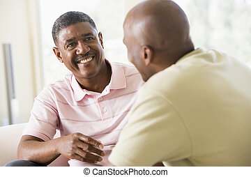 Two men in living room talking and smiling