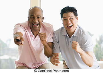 Two men in living room with remote control cheering and...