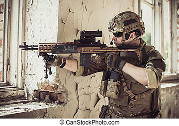 Two men in military camouflage vegetato uniforms with automatic assault rifles