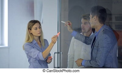 Two men in office discuss plan drawing schemes on glass surface of door.