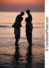 Two men in sea with children on shoulders on sunset