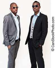 two men standing and wearing sunglasses