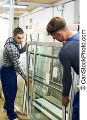 Two men inspecting windows - Two careful workmen checking...