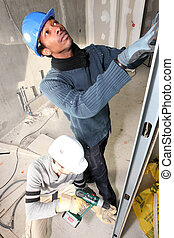 Two men installing dry-wall