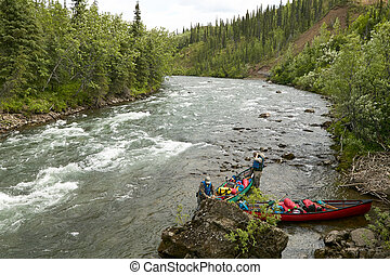 Two men launch canoes beside Alaskan river rapids
