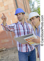 Two men looking at folder of exterior finishings