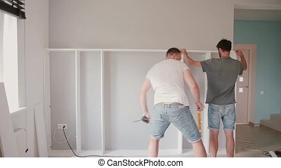 Two men making repair in the bright room. Man helping to his friend moving to new house, assemble furniture together.