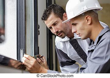 two men measuring a window