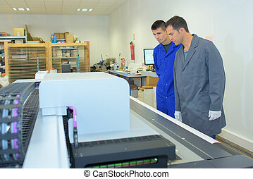 Two men observing printing machine