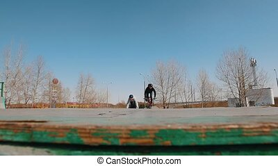Two men on bikes riding in the skatepark performing trick....
