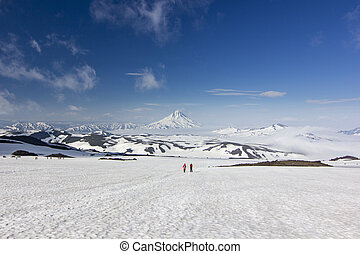 two men on snowy field in kamchatka mountains near covered by snow volcanoes