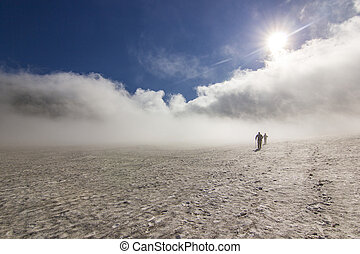 two men on snowy field in kamchatka mountains with clouds and sky above