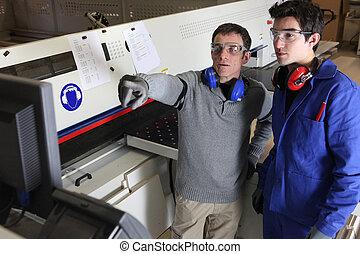 Two men operating factory machine