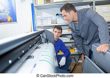 Two men overseeing printing machine