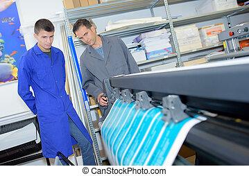 Two men overseeing profesisonal printing machine