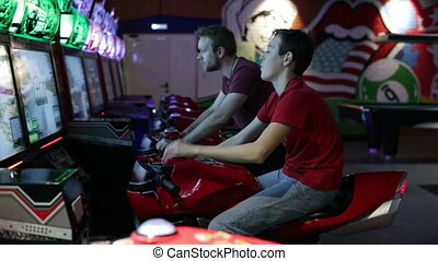 Two men playing arcade racing game on moto - Two friends...