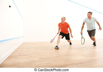 Two men playing match of squash. Squash players in action on...