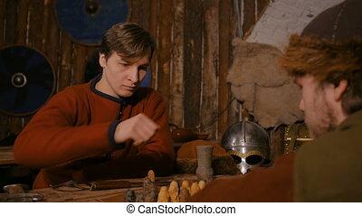 Two men playing popular strategy board game - tafl - Two men...