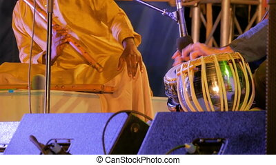 Two men playing traditional Indian tabla drums and flute