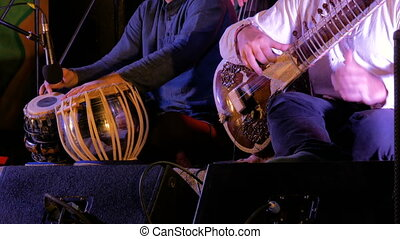 Two men playing traditional Indian tabla drums and sitar
