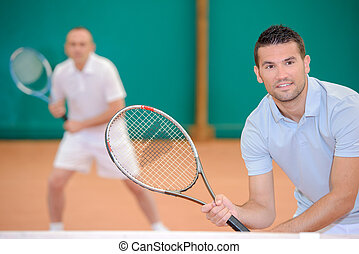 Two men poised for a game of tennis