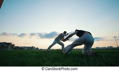 Two men practicing capoeira in grass, summer, at sunset,...