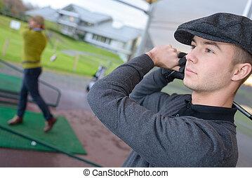 two men practicing golf swing