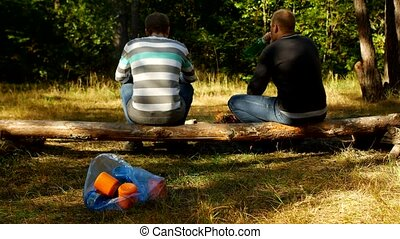 Two men relax in nature and drink alcohol, throw a bottle on...
