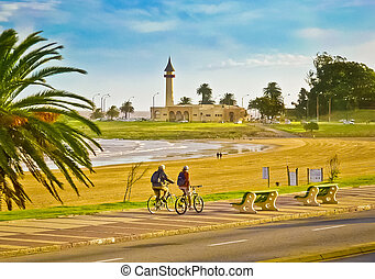 Two men riding bicycles in the sidewalk in fron of a beach located in Montevideo the capital city of Uruguay in South America