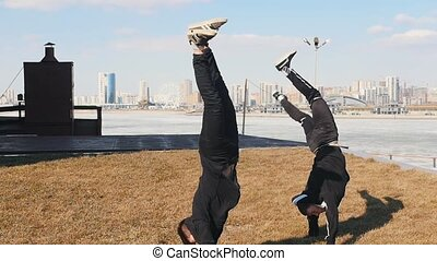 Two men running on the grass and performing a flip. Mid shot