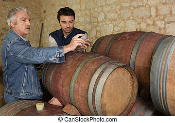 Two men sampling wine in cellar
