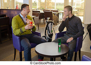 Two men sat in a bar having a drink