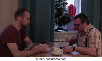 Two men sitting at table eating sushi