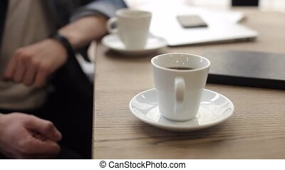 Two men sitting in cafe drinking coffee