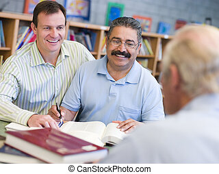Two men sitting in library near another man with a book and notepad (selective focus)