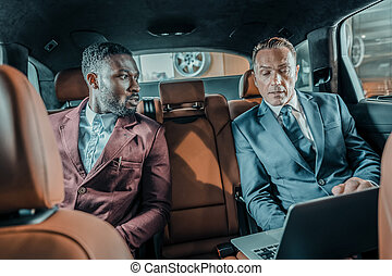Two men sitting on the backseat of the car.