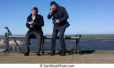 two men sitting outdoors on a bench with a book