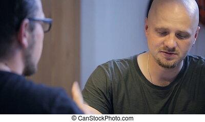 Two men speak with each other sitting in art studio.