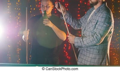 Two men standing by the billiards table and drinking beer while playing. Bearded man in glasses standing rubbing chalk on a cue. Mid shot