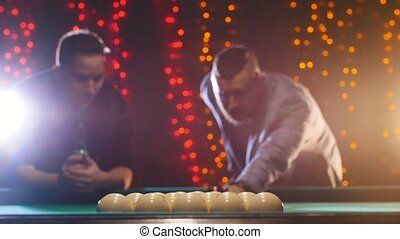 Two men standing by the billiards table, discuss the game...