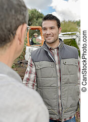 Two men talking, digger in background