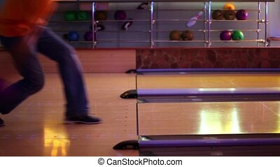 Two men throw bowling ball one by one on parallel lanes in club